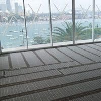 A harbour view from inside of an office with full glass walls, floor covered with a linear carpet.