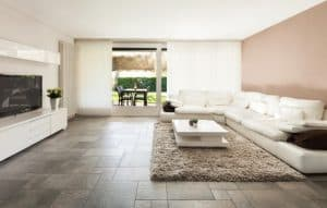 A living room with brown floor tiles fitted with DIY heating kit underneath, a white sofa on right.