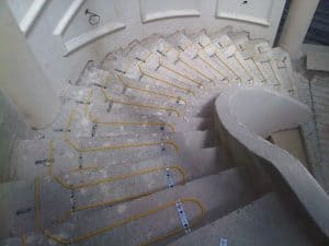 Yellow coloured in-screed twin ducting heating cable installed on the steps of a circular staircase.