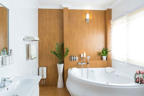 A bathroom with a mirror electric heater on left, a white bath tub on the right, a wooden clad wall.