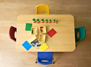 A school table with some playthings kept on it, 4 chairs, on a wooden floor for electric heating.
