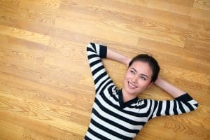 A woman in a black n white striped t-shirt lying on her back a wooden floor, her hands folded, smiling.