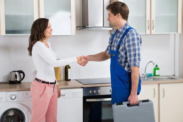 A woman shaking hands with a technician holding a suitcase in kitchen.