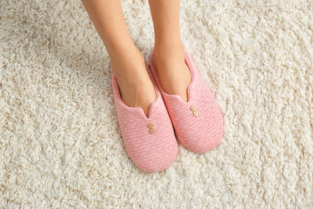Woman in comfortable slippers on warm heated carpet.